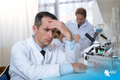 A stressed man in a white lab coat puts his hand on his forehead in frustation. He is sitting at a lab station with a microscope and test tubes filled with red liquid in them. His co-workers yells at someone in the background angrily.