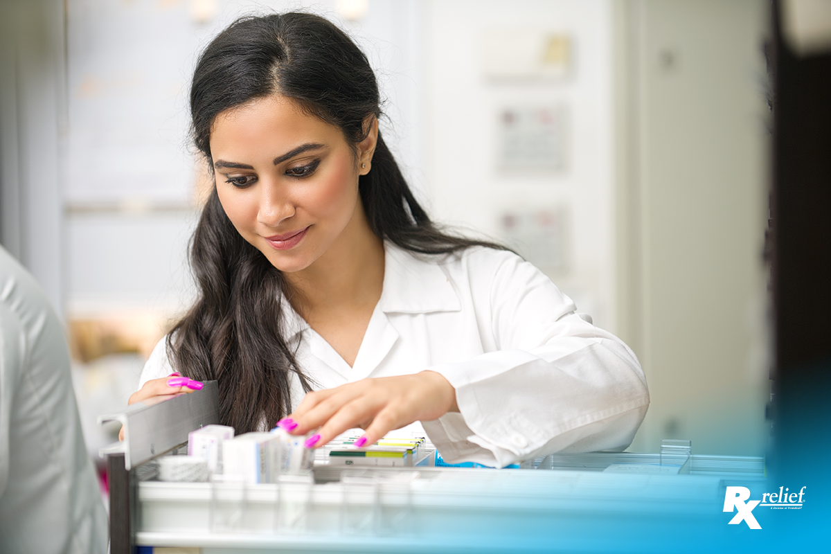Female Middle Eastern pharmacist in white lab coat looks at boxes of medicine in an open drawer.